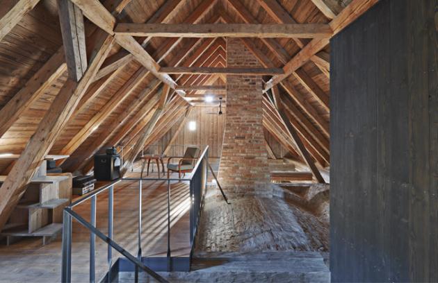 """Tradičně opracované povrchy jsou pro citlivou rekonstrukci typické. Nechybí zde tesané trámy a roubení, ručně štípaný šindel ani hliněné omítky. """"Přírodní materiály a jejich ruční opracování vnášejí do stavby nedokonalost, která se stává zásadním aspektem projektu. Návrh bral už od začátku v potaz nepřesnosti, měnící se tvar a postupné stárnutí…,"""" vysvětluje autorka realizace Lenka Míková"""