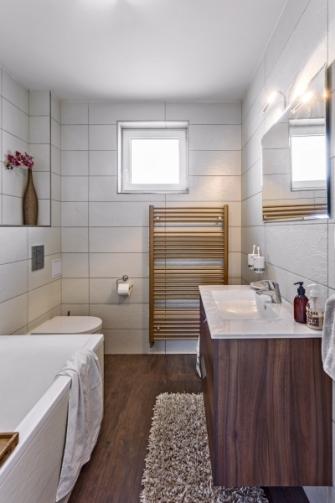 Za zmínku stojí též obklady v koupelně. Jde o dva dekory, obklady ve svislém pásu nad baterií a vanou mají lehce zlacený reliéf, což v kombinaci s osvětlením vytváří hezký světelný efekt