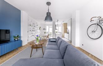 Obývací prostor nezdobí obraz, jak si majitelé původně přáli, ale věšák s kolem. Jde o kolo, na němž sem architekt Martin Machů dojížděl ze svého nedalekého bydliště na kontrolní dny. Je pomyslnou parafou za dokončeným projektem. Je zde umístěna pohovka (Ikea), stolek z bazaru a na míru vyrobená skříňka zhotovená z modře lakované a frézované MDF desky. Modrý prvek umocňuje opakované užití stejné barvy také na stěně
