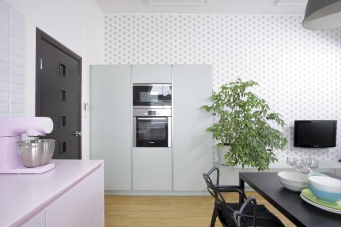Pro vysoký nábytkový modul se spotřebiči zvolil návrhář světle zelený odstín, který příjemně souzní s barevně neutrální tapetou s drobným dekorem značky lavmi