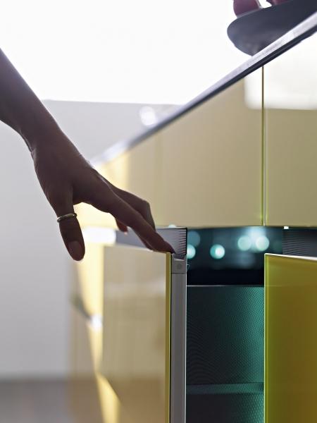 Prstíky malých dětí bývají hbité. Tomu, aby je nelákalo otevírat kuchyňské skříňky, lze zabránit skrytým úchytem otevírání, který je zafrézovaný do horní hrany dvířek. Toto řešení navíc odpovídá trendu minimalistických sestav bez úchytek