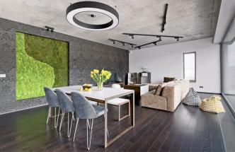 Jídelní stůl vyrobený z kovu a bíle lakovaných masivních prken doplňují nejen klasické čalouněné židle, ale i lavice zhotovená ze stejného materiálu jako stůl. Přehlídku dokonalého řemeslného zpracování kovu a dubových fošen zjemňuje černá textilní tapeta Arte. Všední hrnkové rostliny tu efektně nahrazuje živý obraz z mechu