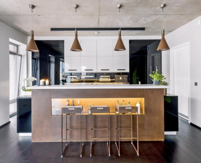 Otevřený společenský prostor propojený s jídelnou a kuchyní si vyžádal uhlazenější vzhled kuchyňského nábytku (Hanák nábytek) zhotoveného na míru, který je sestaven výhradně z černobílé kombinace uzavřených skříněk lakovaných do vysokého lesku. Vestavné trouby a kávovar (Miele) jsou umístěny ve výšce očí v jedné vodorovné linii. Vyvýšený barový pult zhotovený z masivního kusu dřeva a kovu od Vladana Běhala prakticky zastiňuje pohled na pracovní desku v kuchyni