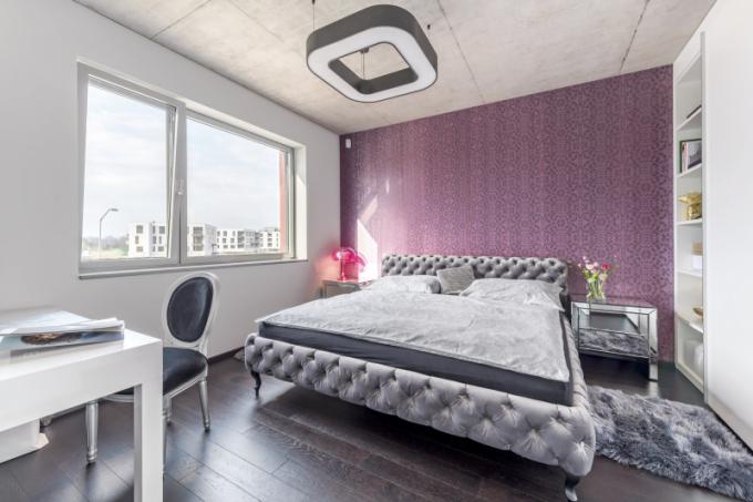 Přestože růžová barva nepatří mezi muži k oblíbeným, akcent růžovofialové barvy tapety je v této ložnici svornou volbou manželů, dělá jim dobře a právě zde spolu se zdobnými tvary a plyšem příjemně vyvažuje průmyslově vyhlížející strop