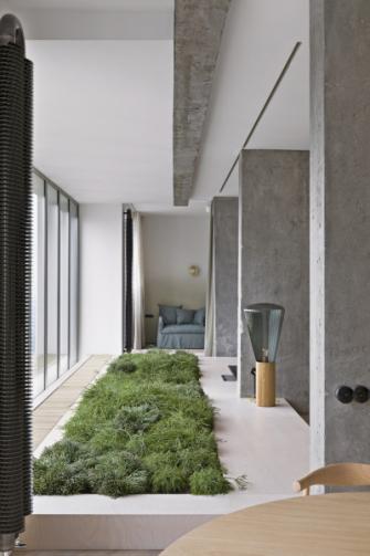 Ruch velkoměsta versus přírodní elementy jsou otisknuty do interiéru prostřednictvím přiznaných betonových panelů a nestandardní interiérové zahrady