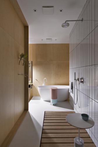 Do koupelny určené pro majitelku byl k volně stojící vaně od značky Agape na míru vyroben integrovaný příruční stolek KEG