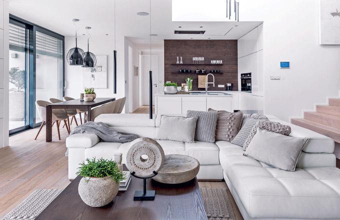 """Kuchyň a obývací pokoj byly na přání investora koncipovány tak, aby vytvářely """"srdce"""" domova. Při otevření pojízdných okenních křídel na terasu, které tvoří prakticky celou stěnu, lze dosáhnout absolutního sepětí s okolní přírodou"""