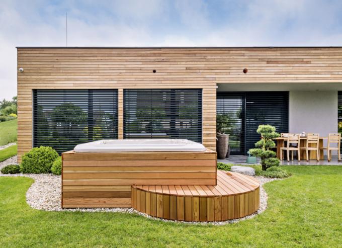 Strohou geometrii domu skvostně doplňuje zahrada s kulatými keři a kamennými doplňky a luxusní whirpool (design Žaneta Radiměřská) vloženého do speciálního designového kulatého krytu. Obytné zázemí se zahradou je uzavřené gabionovým plotem, jehož výplň tvoří kulatý pískovec