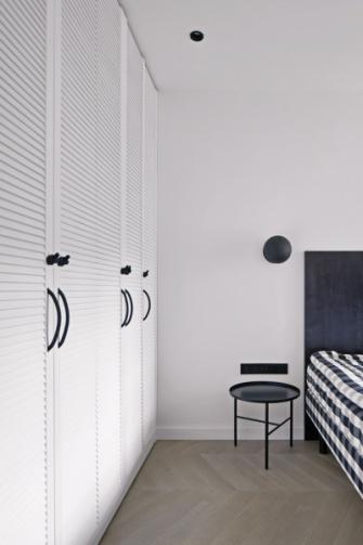 V ložnici převládá bílá barva. Přílišnou uhlazenost příjemně narušuje plasticita dveří šatních skříní