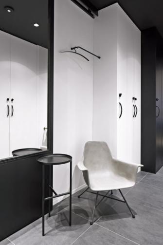 Ve vstupním prostoru bytu je použita dlažba, jejíž odstín společně s barvou betonové židle zklidňuje kontrastní kombinaci černé a bílé
