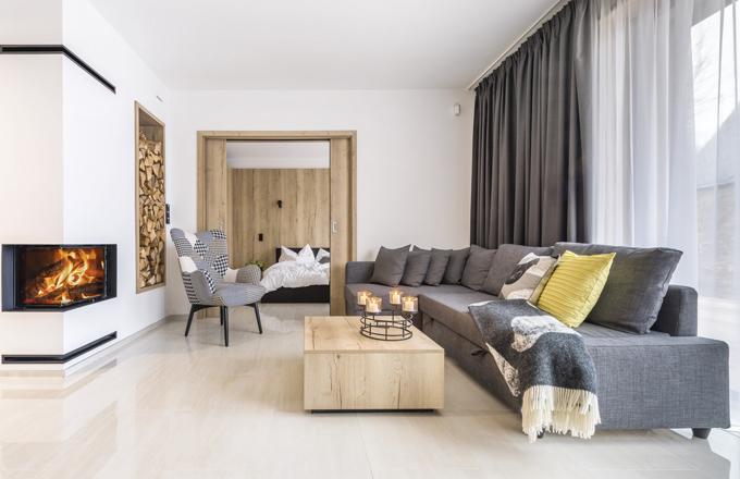 Obývacímu prostoru dominuje rozkládací sedací souprava (IKEA). U krbu je možné posedět v efektně čalouněném ušáku (Kika). Posuvné dveře do master ložnice umožňují nejen přístup, ale i optické zvětšení prostoru
