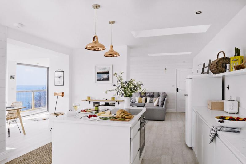 V centru kuchyňské části je ostrůvek s prostornou pracovní deskou, která se dvěma barovými židlemi poslouží jako alternativa jídelního stolu