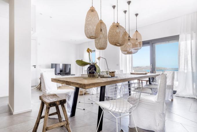 Ocelové nohy jídelního stolu odkazují na kónický tvar obvodového zdiva. Atraktivní svítidla z přírodní trávy nad jídelním stolem dokonale propojují interiér s exteriérem