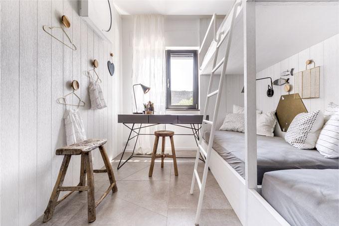 Dětský pokoj je vybaven nábytkem zhotoveným na míru. Dvě postele s palandami umožňují pobyt čtyřem dětem. Pokoj je doplněn pracovním stolem, nástěnnými košíky, háčky a zlatými ramínky (vše Hübsch)