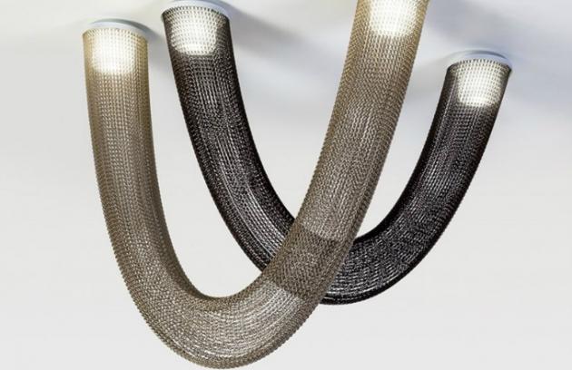 Svítidlo Aura (Kriskadecor) tvoří sestava světelných zdrojů propojených závěsy z hliníkových řetězů.  Vytváří tak dojem jasně směřovaného proudu světla, které vybočuje pouze v podobě jemného svitu procházejícího skrz drobný pletenec. Konstrukce je vyrobena z lakovaného kovu, difuzory jsou z matného opálového skla. Design Yonoh.