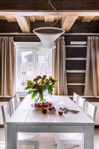 Bíle lakovaný dřevěný stůl Nantes z dubového masivu doplňují židle Praga ze stejného materiálu (obojí Altacorte). Nevšední materiálový kontrast vytvářejí společně s plastovým svítidlem (Deltalight)