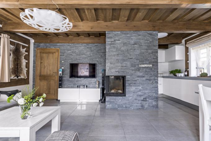 Vyhřívanou podlahu kryje lapovaná keramická dlažba (60 × 60 cm). Stěna krbu je obložena štípanou břidlicí