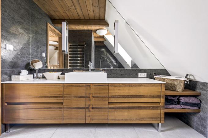 Koupelna v patře zahrnuje akrylátovou vanu (Riho) a klozet (Duravit). Stěna za mořenou dubovou skříňkou s umyvadlem Vero (Duravit) je obložená zrcadlem. Odrazem opticky zvětšuje místnost