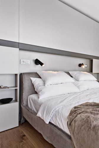 Čelo postele tvoří nika obstavená úložným prostorem s integrovaným osvětlením