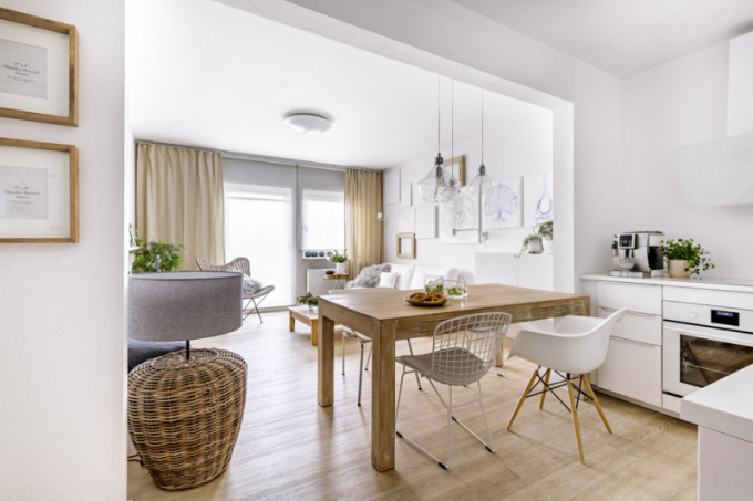 V hlavním obytném prostoru kraluje velký masivní stůl z akácie upravený bílým voskem a čtyři ikonické židle v bílé barvě Foto popis| Kuchyň (IKEA) je zhotovená z bíle lakované MDF desky podle návrhu designérky Markéty Fleischnerové. Bílou barvu mají i vestavné spotřebiče – varná deska a pečicí trouba a také digestoř. Na stěně za pracovní desku je použita speciální matná omyvatelná bílá barva odolná proti oděru (Prokeran, Hornbach)