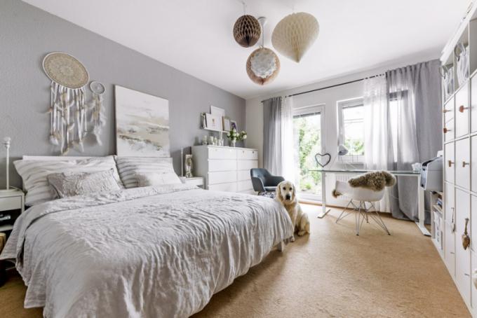 Ložnice slouží současně jako pracovna, z níž je možné vyjít přímo na terasu a do zahrady stejně jako z obývacího pokoje. Pracovní stůl (IKEA) je doplněn Eames Plastic Armchair DAR (Vitra). Prostorné lůžko zdobí v záhlaví abstraktní obraz a lapače snů, které si designérka sama zhotovila. Stříbrné vázy pořídila ve firmě Hitra