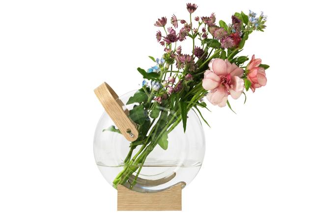 """Váza Handle (Mater) se rychle stane ozdobou každého stolu. Dřevěná základna umožňuje hrát si s polohou vázy, což usnadňuje aranžování květin, a rukojeť zase usnadňuje přenášení z místa na místo při hledání """"toho pravého"""" místa pro ni. Vyrobena je z ručně foukaného borosilikátového skla a dubu s certifikátem FSC. Design Eva Harlou, 18 × 20 × 7,5 cm, cena od 3 015 Kč, WWW.STOCKIST.CZ"""