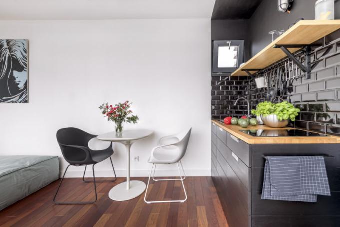 Do obývacího ateliérového celku je zasazená kompaktní, ale velmi praktická minikuchyňka, jejíž místo vyčleňuje černá barva propisující se i na stropě