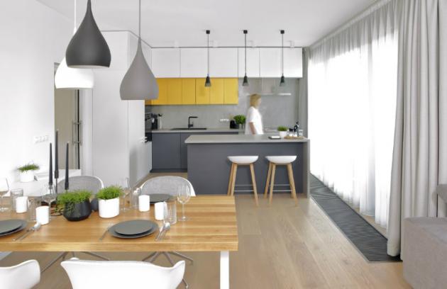 Barevně vyvážený interiér působí elegantně a stylově čistě. Neutrální barevné řešení oživují skříňky v tlumeném žlutém odstínu