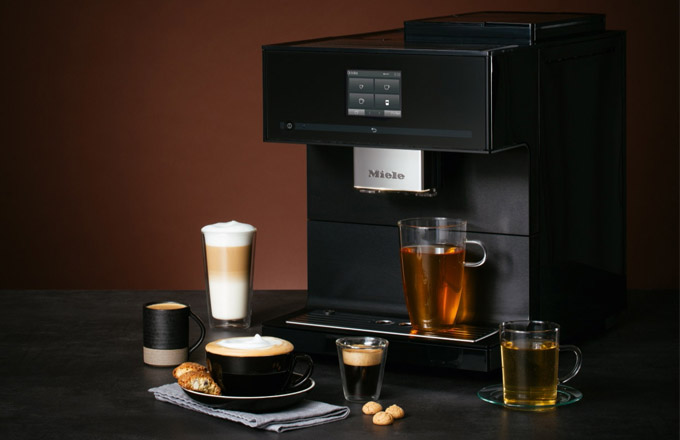 """Na IFA 2018 se dočkali i milovníci skvělé kávy. Nový volně stojící kávovar CM 7750 CoffeeSelect, který nabízí čtyři užitečné funkce, dostupné pouze u Miele. Pouhým stiskem tlačítka můžete zvolit jeden ze tří různých druhů kávy, a jistě oceníte i tichý chod kuželového mlýnku znerezové oceli, který mele jemně a beze zbytků, nebo automatické odvápňování a senzorové čidlo, jež nastavuje výšku trysky nad šálkem. Kávový labužník si navíc může vybrat ze 16 kávových specialit, jako je káva, espresso, cappuccino nebo latte macchiato, speciality """"Long black"""" nebo """"Flat white""""."""