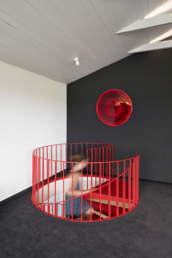 Interiér vtipně doplňuje i červený kruhový obraz od Milana Hausera z galerie Kvalitář, zavěšený nad točitým schodištěm.