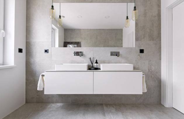 Vše, co je v koupelně zapotřebí, je uloženo v široké umyvadlové skříňce zhotovené na zakázku. Kromě okna prostor opticky prosvětluje velké nástěnné zrcadlo