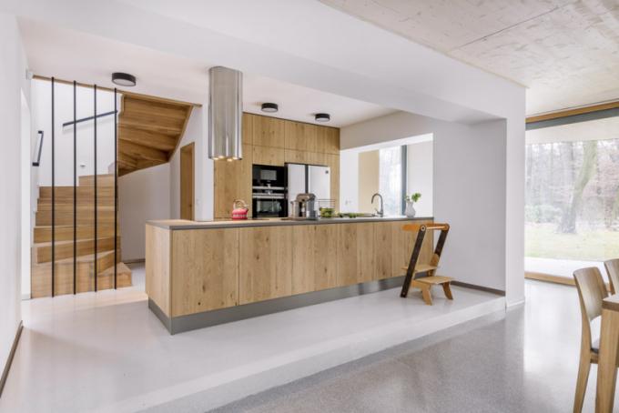 Opticky přiznaná kuchyňská zóna nabízí velkorysé úložné prostory, další kuchyňské zázemí pro uskladnění potravin se skrývá za dveřmi pod schodištěm