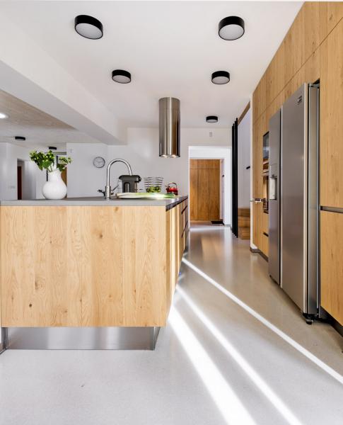 Jednotícím prvkem interiéru je dubová dýha, v kuchyni kombinovaná s kovovými plochami
