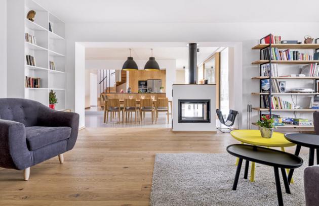 Kuchyňská, jídelní a obývací zóna jsou od sebe odděleny pomocí nízkého schodu tak, aby prostor působil vizuálně kompaktně. Kuchyň je vyrobena na míru z dubového dřeva