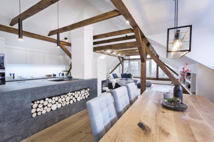 Kuchyň je vyrobena z vysoce odolného bílého lamina v kombinaci s imitací betonu. Do pracovního pultu je zasazen granitový dřez (Blanco). Ostrůvek ozvláštňuje praktická nika vyplněná dekorativním dřevem. Za kuchyňskou linkou září osvětlené bílé sklo, které prostor opticky nezatěžuje a lze ho snadno udržovat. S ohledem na nedostatek místa jsou židle na jedné straně jídelního stolu nahrazeny lavicí. Vše je zhotoveno na míru podle návrhu designérky. Celek dotváří svítidlo Charterhouse (Eglo)