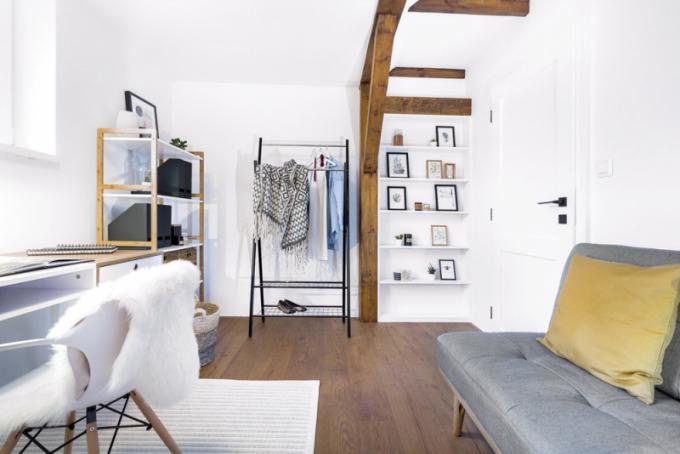 Domácí pracovna se stolem Linus slouží příležitostně také jako hostinský pokoj. Je vybavena rozkládací pohovkou a praktickým štendrem. Zajímavým elementem jsou vestavěné police v trámové konstrukci po pravé straně dveří a stírací mapa nad pohovkou, do níž si manželé mohou značit místa, která už procestovali
