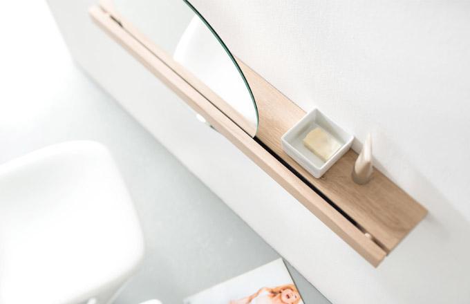Nástěnné zrcadlo Saw (Sudbrock) elegantně prostupuje otvorem v polici z dubového dřeva, po jejíž délce jím lze posouvat do obou stran. Pohyb rotací odkazuje na inspiraci v podobě pily zdolávající kusy masivního dřeva. Design Michael Hilgers, www.sudbrock.com