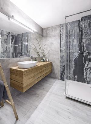 Původní obklad koupelny je překrytý stěrkou. Sprchový kout je s ohledem na pravidelný a intenzivní kontakt s vodou obložený velkoformátovou keramickou dlažbou (120 × 120 cm). K umyvadlu (Ideal Standard) je připojena stojánková baterie (Hansgrohe). Ručníky je možné zavěsit na bambusový žebřík (Broste)