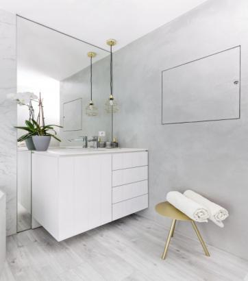 Druhá koupelna je vybavená vanou. Skříňka se zapuštěným umyvadlem (Duravit) je opatřena bílou kompaktní deskou. Částečně je obložena velkoformátovou keramikou s imitací světlého mramoru a stěrkou. Součástí místnosti je i klozet