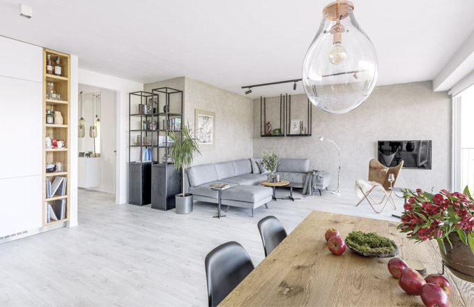 Obývací pokoj je vybaven na míru skříňkami s otevřenými policemi zhotovenými z dubové dýhy a lakovaných kovových profilů. S ohledem na snadnou údržbu a odolnost zvolili manželé vinylovou podlahu