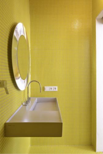 Drobná mozaika ve žluté barvě prostor opticky zvětšuje