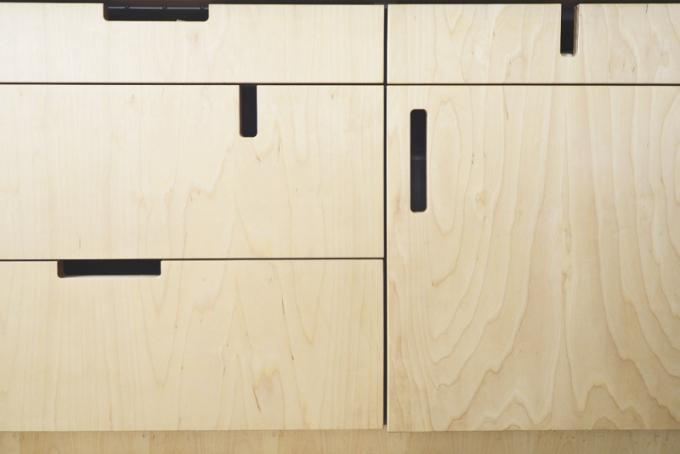 Vtipným detailem jsou asymetricky vyřezané otvory ve dvířkách kuchyňské linky vyrobené na míru