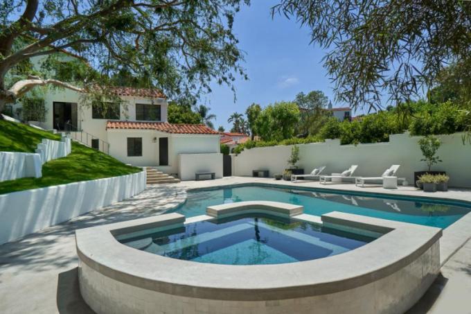 Bazén je obklopený vzrostlými stromy a udržovaným trávníkem.