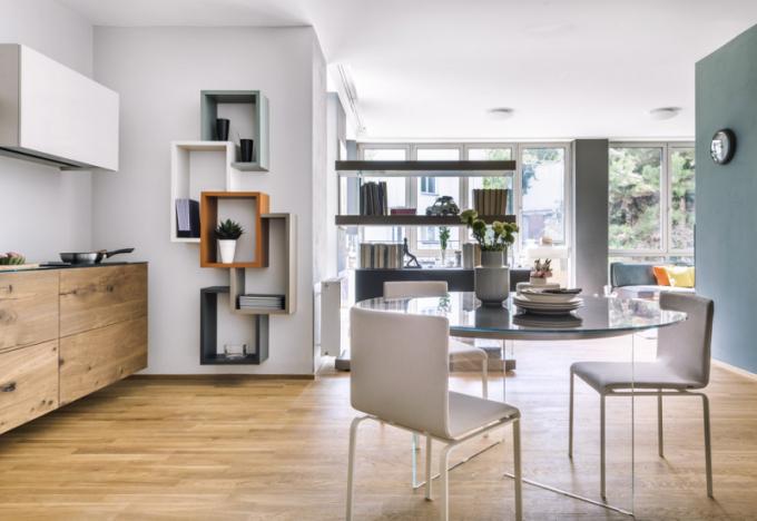 Kuchyňské zázemí je propojeno s jídelní zónou pro chvíle tzv. expres snídaní či rychlých snacků tak, aby paní domu měla komfort při servírování. Jídelní nábytek je laděn v obdobně minimalistickém duchu jako kuchyň, stůl Air je zajímavý řešením základny, která je z transparentního materiálu a vytváří dojem levitující jídelní plochy vyrobené z lakovaného kaleného skla, doplněné o židle Dangla, vše od italského výrobce Lago