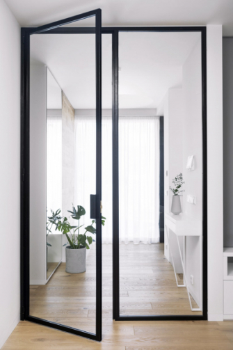 Koncepce velkých čistých ploch je doplněna o celoprosklené dveře, vyrobené zámečníkem na míru