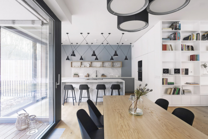 Jídelní stůl byl vyroben na míru z dubového dřeva tak, aby korespondoval s pokládkou podlahy, a je doplněn o židle od tradičních skandinávských značek Muuto a Menu, stropní osvětlení nad jídelním stolem je od výrobce Zeitraum