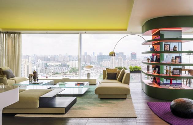 Stropní výklenek vežluté barvě opticky zvětšuje prostor, tvoří efektní přechod doexteriéru avhodně doplňuje syté odstíny zelené afialové nakobercích anábytku. Vcelém interiéru je mnoho ikonických kusů nábytku adoplňků. Nechybí ani stojací lampa Arco nebo stolní lampa Taccia, obojí oditalského výrobce Flos