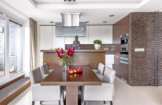 Jídelní stůl navazuje na varný ostrůvek a vzhledově je propojen s vyvýšeným parapetem, který tvoří předěl mezi kuchyní a jídelnou