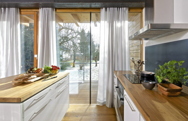Celý interiér je materiálově sladěný. Dubové dřevo napodlaze, rámech aterase je použité inapracovní desce. Kovová traverza nad okny koresponduje socelovým plátem použitým naobložení kuchyňského zádového panelu