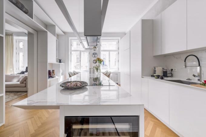 Kuchyňská zóna je přirozeně propojena sjídelní zónou. Pro její výrobu architekti zvolili lakovanou bílou MDF vmatu vkombinaci spracovní deskou zvelkoformátové tenké dlažby vmramorovém dekoru